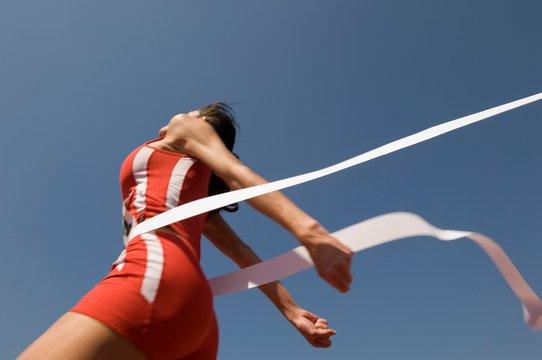 Female Athlete Crossing Finish Line Against Blue Sky