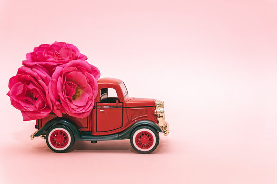 Red toy truck delivering bouquet of rose flowers on pink background. February 14, Valentine's day, 8 March, International Women's Day. Flower delivery. Copy space