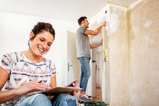 Young couple making plans while renovating the new dwelling