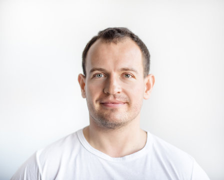 Closeup portrait of serious 30 years old caucasian white man on white background in white t-shirt. Confident happy smart modern man looking in camera. Lifestyle