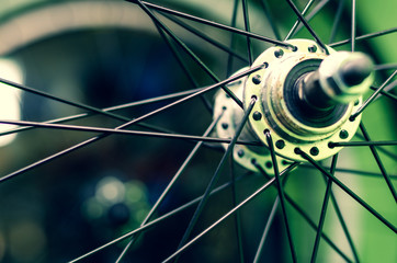 Bicycle repair workshop. On the hook hang new wheels. The hub is black and the spokes and rim are...