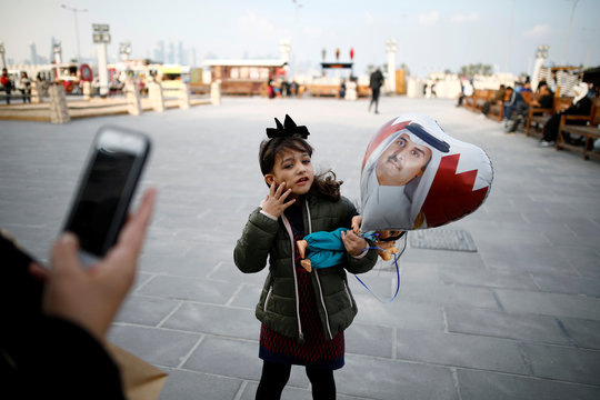 A girl poses for a photo while holding a balloon with the picture of Qatar's current Emir, Sheikh Tamim bin Hamad Al Thani, at Souq Waqif, a marketplace in Doha