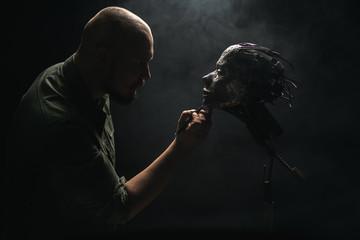 Man holding ornamental metal skull