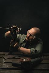 Focused artisan creating metalwork with instrument