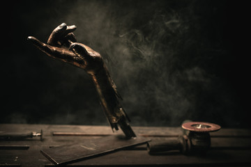 sculpture of a metal hand with smoke on the background
