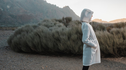 Faceless Model Wearing Futuristic White Coat In The Volcanic Scenery