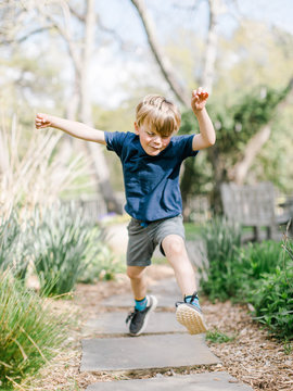 Little boy leaping over stones