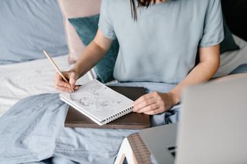 Crop woman sketching on bed