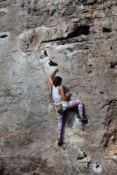 Sportive woman hanging on rock