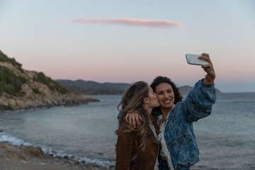Two girls taking a selfie together by the sea