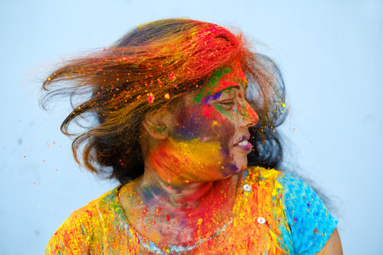 Young woman playing with her hair full of color powder during holi celebration