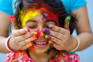 Mother smearing color powder on her daughters face during holi celebration,portrait