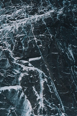 Detail of black rock with snow in arctic island