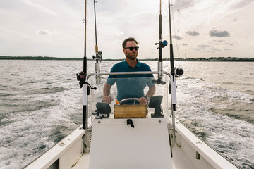 Outdoor Active Lifestyle of man Driving Boat in Fall
