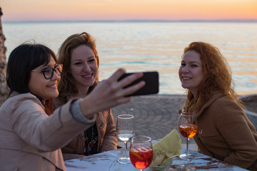 Beautiful young women chilling together by the lake and taking selfie
