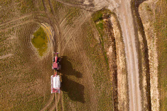 Tractor with trailer riding in field