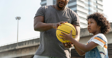 Father teaching son to play basketball