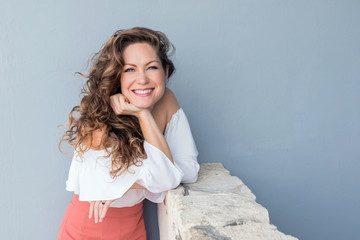 Attractive smiling woman leaning on wall