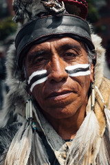 Native American portrait - mature face-painted man in a traditional outfit