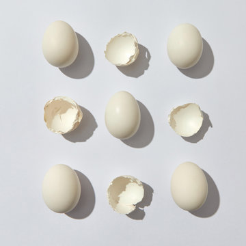 Composition of whole eggs and eggshell halves on a gray background with copy space. Flat lay