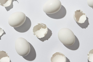 Pattern of white eggs and eggshell on a gray background with shadows. Flat lay