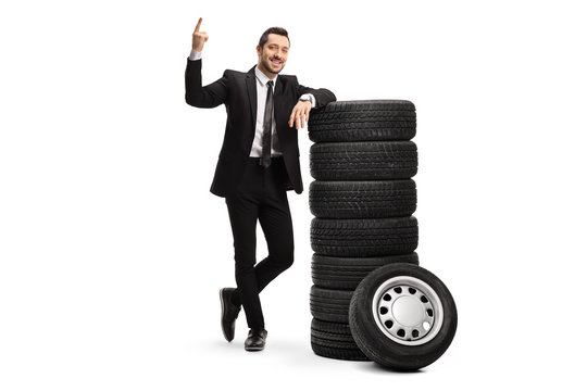 Young businessman pointing above and leaning on a pile of car tires