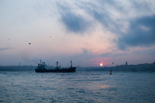 Cargo boat floating in sea and cloudy sky at sunset. Sunset on the Bosphorus channel