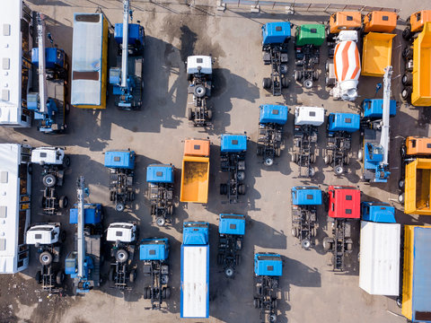 Construction machines empty dump trucks, cement mixers, tow trucks with hard shadows on a parking. Aerial top view from drone.