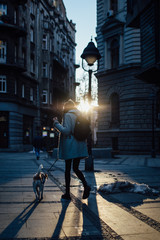 Outdoor portrait of beautiful blonde woman walking a dog