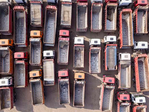 Aerial view from drone empty dump trucks on a rest stop with shadows. Top view in a sunny day.