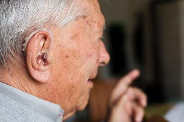 Senior man wearing hearing aid tool