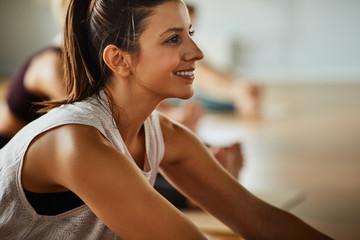 Smiling woman relaxing on a gym floor after yoga class