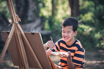 Asian boy with Down's syndrome is happily drawing a picture of an elephant in the garden.Drawing, Art Therapy