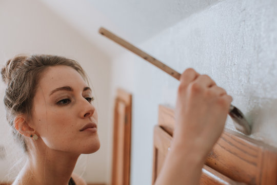 Woman Painting Wall Carefully