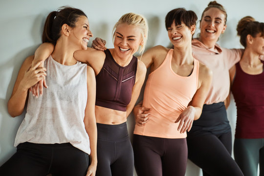 Female friends laughing together while standing in a gym