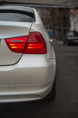 Detail of the rear light of a white car.