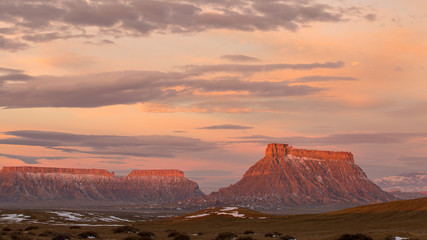 Wall Murals Salmon Colorful sunrise over Factory Butte in the Utah desert with vibrant clouds in the sky.
