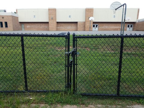 locked gate and basketball court and school building