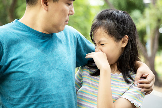 Foul-smelling man was hugging her daughter while her child girl can smell the armpit smelly or the body odor foul from her father with closing her nose,feel stinks,asian male sweat from hot weather