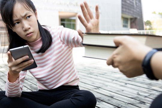 Asian child girl is avoiding reading book,she wants to use a mobile phone,addicted to smartphone,teenage student is refusing to read books, learning disorder,attention deficit,hyperactivity disorder