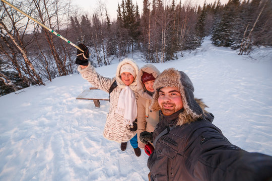 Happy family takes a selfie in the winter forest.
