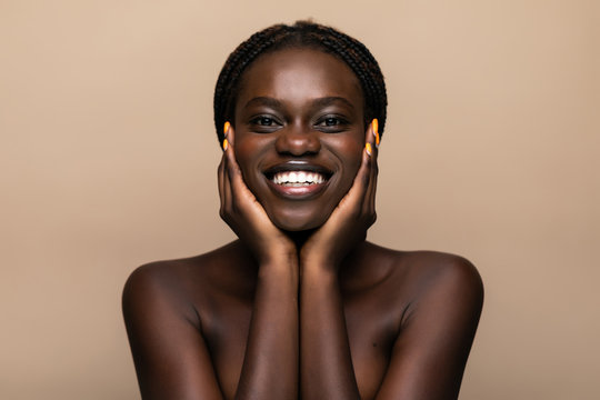 Young african girl with perfect skin on beige background. Beauty Skin care concept