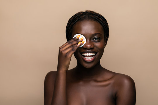 Close up portrait of an attractive african american woman removing makeup with sponge isolated on beige background