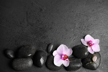 Tuinposter Orchidee Stones with orchid flowers and space for text on wet black background, flat lay. Zen lifestyle