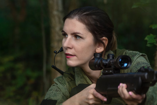 Portrait of beautiful army girl, soldier woman with rifle with optical sight and military uniform in the forest
