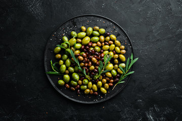 Olives in a bowl, olive oil, spices and herbs. Top view. Free space for your text.