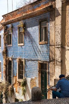 Reading tourist in Alfama district, Lisbon, Portugal