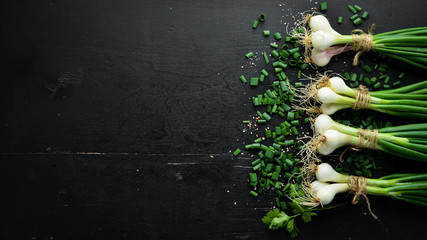 Fotomurales - Green onion on a wooden table. Fresh vegetables. Top view. Free space for text.