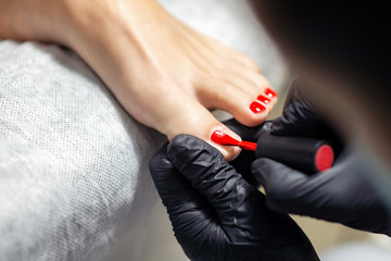 Fotorolgordijn Pedicure Hands in black gloves are doing red pedicure or manicure on woman's toes, close up.