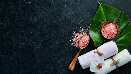 Pink sea salt with towels and tropical leaf. On a black stone background. Spa treatments. Top view. Free space for your text.